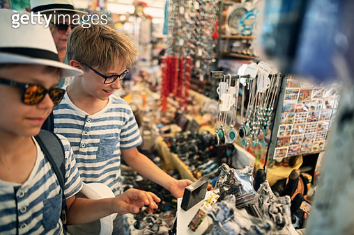 Kids and grandmother browsing and buying souvenirs at street market stand in Pompeii, Campania in Italy. - gettyimageskorea