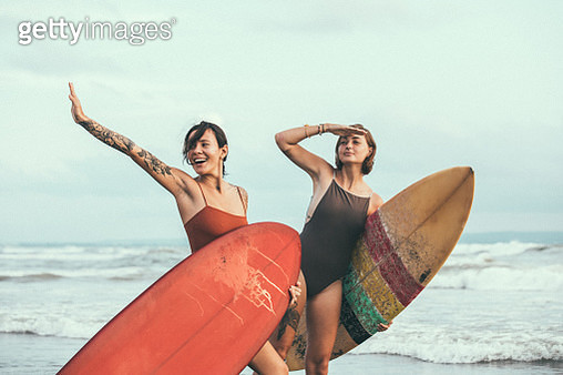 Pretty young surfers at the beach - gettyimageskorea