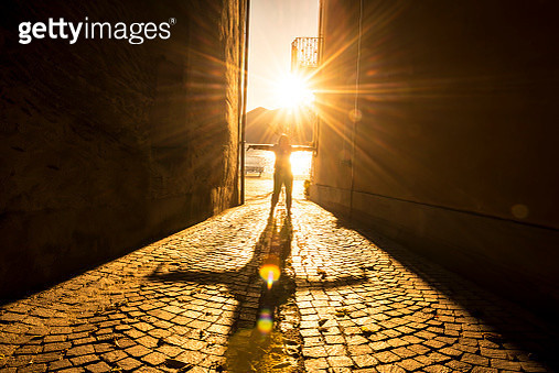 Woman with Arms Outstretched in a Narrow Street with Sunbeam and Shadow in Ascona, Switzerland. - gettyimageskorea
