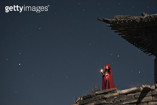 Woman standing on Chinese Ancient Architecture viewing Starry sky .-Halloween theme - gettyimageskorea