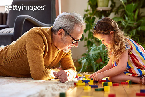 Mature man lying on floor playing with little girl, support, assistance, learning - gettyimageskorea