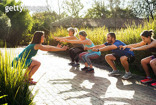 Shot of a group of people exercising together outdoors in park with female trainer demonstrating the workout - gettyimageskorea