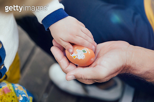 Toddler giving his grandfather an Easter egg, close-up - gettyimageskorea