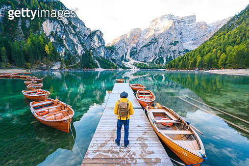 One man standing on a pier at lake Braies, South Tyrol, Italy - gettyimageskorea
