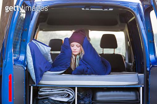 A beautiful traveler gets cozy inside her van. - gettyimageskorea