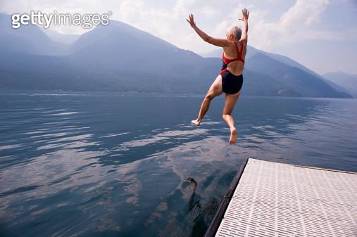 female babyboomer jumping into lake - gettyimageskorea