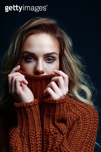 Fashion portrait of long hair blond young woman wearing brown sweater, looking at camera and covering mouth. Studio shot against black background. - gettyimageskorea