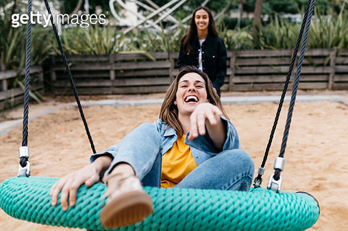 Two friends on playground, woman on a swing - gettyimageskorea