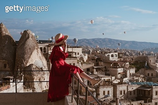 Woman Sitting On Railing Against Sky At Cappadocia - gettyimageskorea