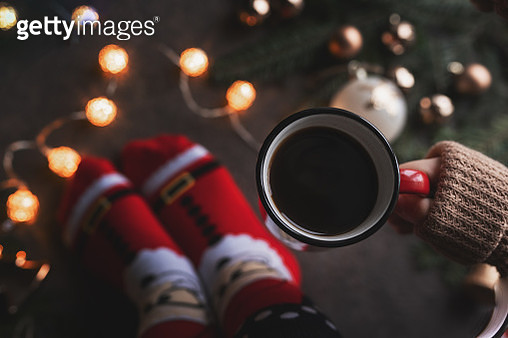 Woman holding in hands hot christmas tea with candy cane against decorations, gift boxes, ribbon and ginger bread on wooden board. Xmas concept. Eye bird view. - gettyimageskorea