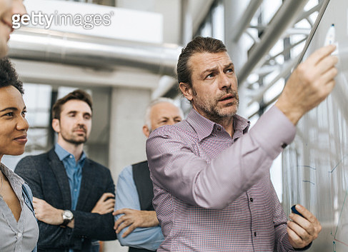 Mid adult entrepreneur drawing business development to his colleagues on whiteboard. - gettyimageskorea