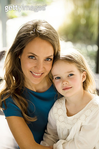 Portrait of smiling mother with daughter in front of window - gettyimageskorea