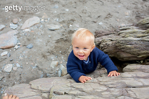 Beautiful baby boy on a rocky beach on a cloudy day, shot from above - gettyimageskorea