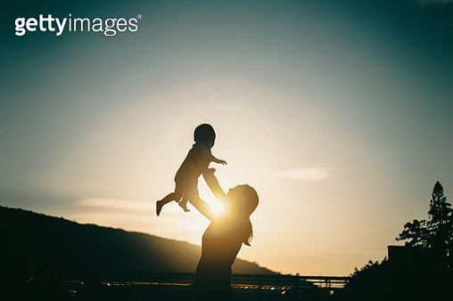 Silhouette of mother raising baby girl in the air outdoors against sky during a beautiful sunset - gettyimageskorea