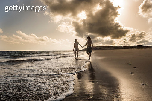 Man And Woman Holding Hands At The Beach During Sunset - gettyimageskorea