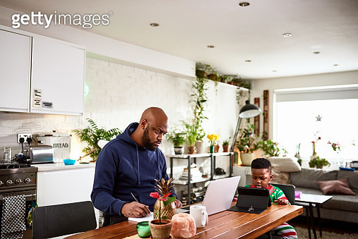 Father and son sitting at kitchen table, man using laptop, boy on digital tablet, technology, connections, role model - gettyimageskorea