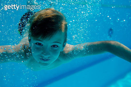 Young boy is diving in a pool - gettyimageskorea