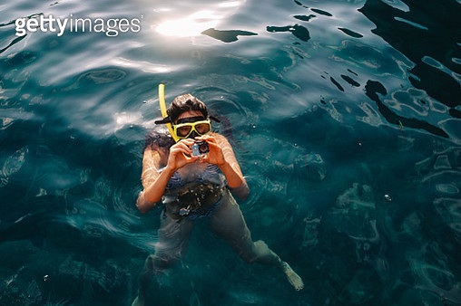Young woman setting up her action camera for snorkeling - gettyimageskorea