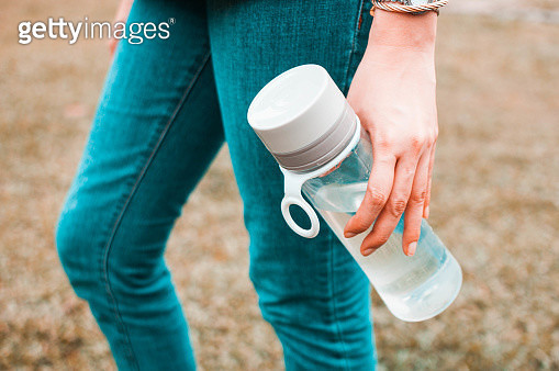 A close-up view of a young woman holding a reusable water bottle container outdoors - gettyimageskorea