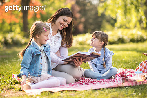 Mother telling a story to her little girls in spring day. - gettyimageskorea