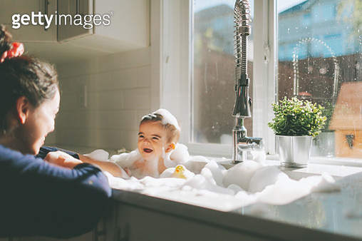 Cheerful Baby Boy In Bathtub Looking At Mother - gettyimageskorea