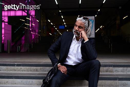 Stylish senior businessman sitting on stairs outdoors - gettyimageskorea