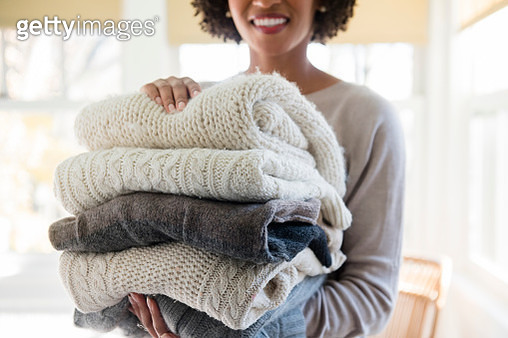 Woman holding stack of folded sweaters - gettyimageskorea