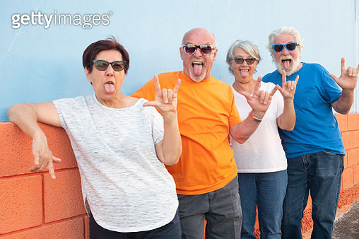 Portrait Of Senior Couples Sticking Out Tongue And Gesturing Against Wall - gettyimageskorea