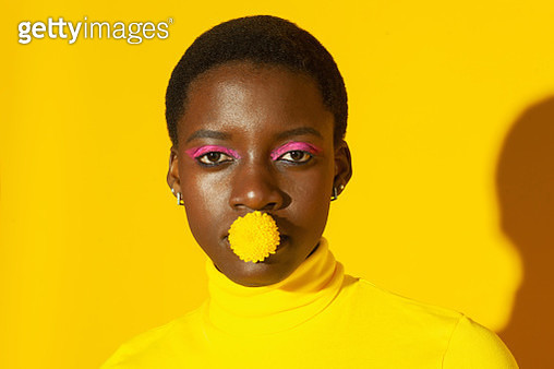 close up portrait of young female with yellow flower in mouth - gettyimageskorea