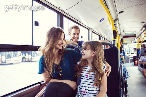 Mid adult woman traveling with daughter in bus. Girl is commuting with mother in public transport. Father sitting in the background, looking at his family. - gettyimageskorea