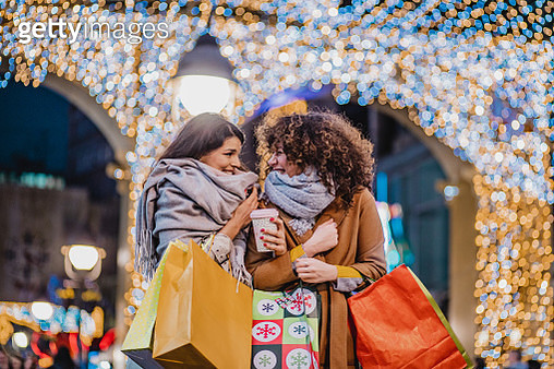 Two excited female friends in a holiday shopping - gettyimageskorea