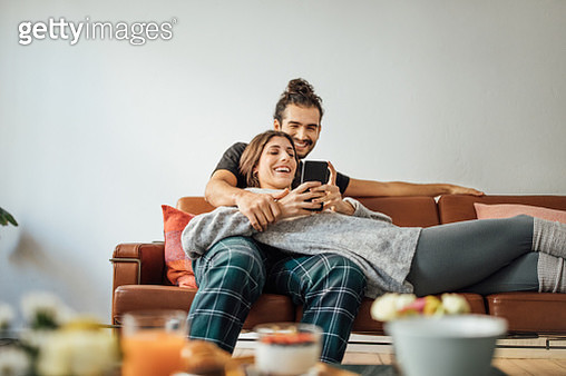 Young couple with smart phone relaxing on sofa - gettyimageskorea