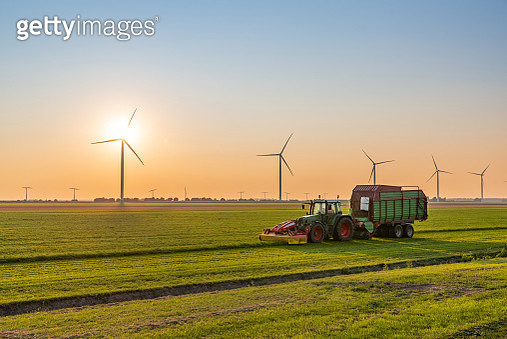 Tractor with trailer harvesting on a field near wind turbines at sunset - gettyimageskorea