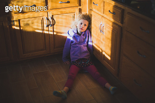 Girl Sitting on Kitchen Floor - gettyimageskorea
