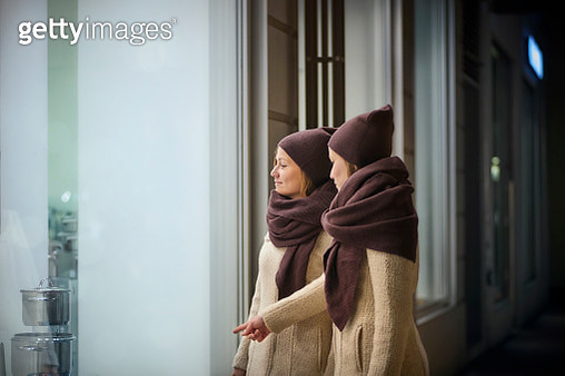 Two young women looking at shop window - gettyimageskorea