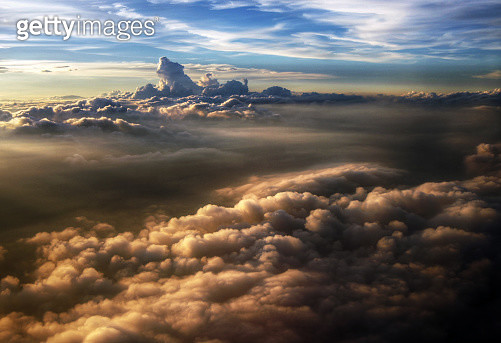 Sunset above stormy clouds view from airplane - gettyimageskorea