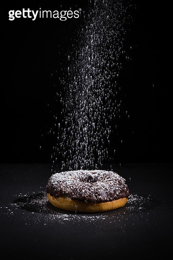 Sprinkling sugar powder on delicious donut topped with chocolate - gettyimageskorea