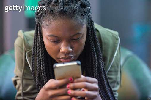 Young woman intently reading cell phone - gettyimageskorea