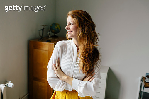 Smiling young woman in office looking sideways - gettyimageskorea