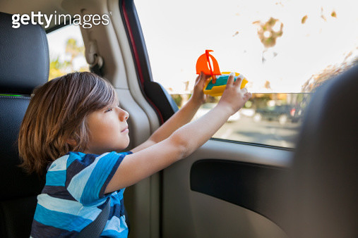 Young boy holding toy boat in mini van - gettyimageskorea