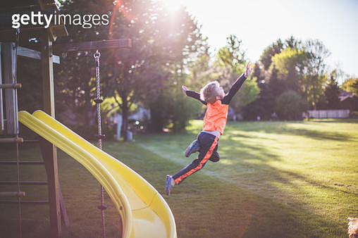 Little boy Leaping from a Jungle Gym Slide - gettyimageskorea
