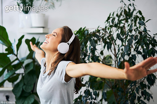 Happy young woman with oustretched arms listening to music at indoor plant - gettyimageskorea