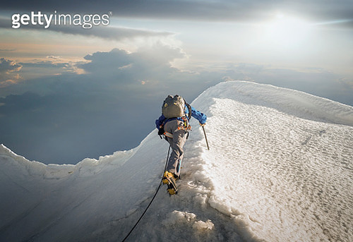 A lone climber ascending a snowy ridge in the Alps - gettyimageskorea