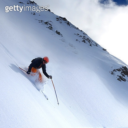 Male extreme skier riding backcountry in the deep snow on a sunny day in St. Anton, Austria - gettyimageskorea