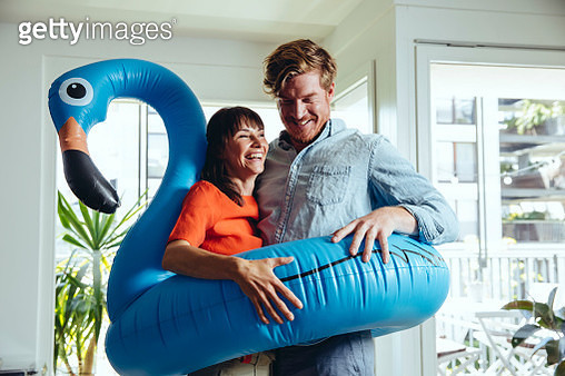 Happy couple holding an inflatable flamingo at home - gettyimageskorea