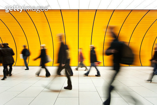 People blurry in motion in yellow tunnel down hallway - gettyimageskorea