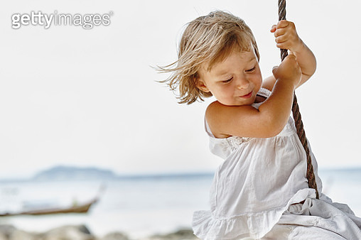 Thailand, Phi Phi Islands, Ko Phi Phi, happy little girl on a rope swing on the beach - gettyimageskorea