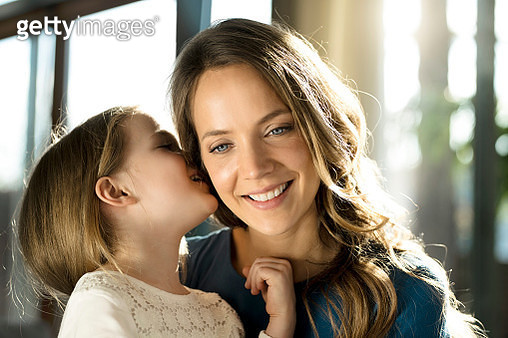 Smiling girl whispering into her mothers ear - gettyimageskorea