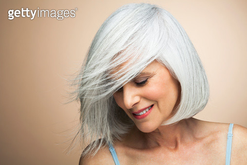 Mature woman with silvery, grey hair styled in a bob in front of beige background with wind blowing across her face looking down smiling. - gettyimageskorea