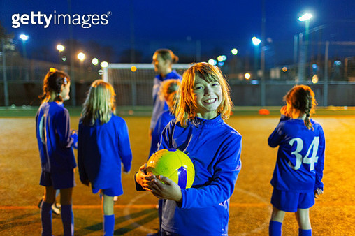 Portrait smiling, enthusiastic girl enjoying soccer practice on field at night - gettyimageskorea
